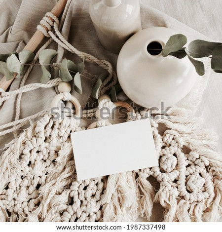 Card mockup with copy space in Boho style interior, still life scene on beige neutral background.  Makrame, vasen, eucalyptus leaves.Top view. Foto stock ©