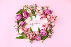 Card with calligraphic quote «Be beautiful» on pink background. Rose buds and green leaves round frame wreath, flat lay, top view.