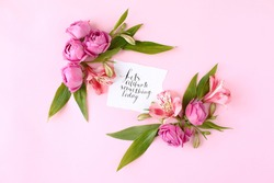 Card with calligraphic quote «Let's celebrate something today» on pink background. Rose buds and green leaves frame, flat lay, top view.