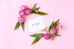 Card with calligraphic words «Be happy« on pink background. Rose buds and green leaves frame, flat lay, top view.