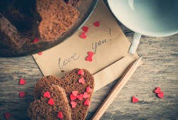 Card with Message Love You on the Letter and Chocolate Cookies Shape of Heart at Valentine's Day