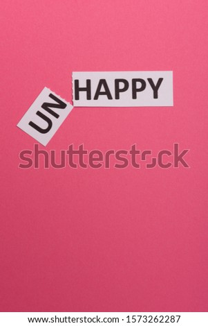 card with text unhappy, cutting word 'un' so it written 'happy'. Copy space. Lime background. Studio shoot.