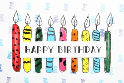 Card with words HAPPY BIRTHDAY and colorful drawn candles on paper sheet, top view