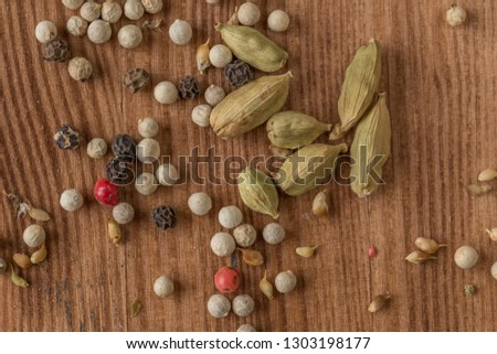 cardamom,  allspice (sweet peas), red pepper, white pepper and seeds on a natural wooden surface. Flat lay. Food concept.  #1303198177