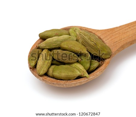 cardamom in a wooden spoon over white - stock photo