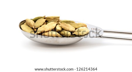 Cardamom pods measured in a metal tablespoon, isolated on a white background