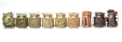 Cardamom, star anise, cinnamon, clove, coriander seed spices and dried bay leaves, parsley, thyme, rosemary herbs in mason jars over white background