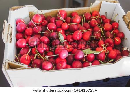 Cardboard box full of freshly harvested fresh cherries #1414157294