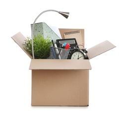 Cardboard box full of office stuff on white background