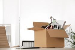 Cardboard box full of stuff on table in office