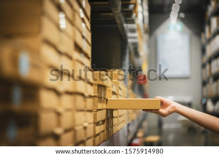Cardboard box package with blur hand of Asian shopper woman picking product from shelf in warehouse. customer shopping lifestyle in department store or purchasing factory good concepts. Stock foto ©