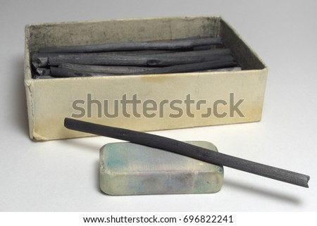 cardboard box with natural charcoal sticks and dirty eraser. Good old art materials