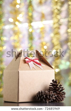 Cardboard box with pine cones next to it.