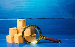 Cardboard boxes and magnifying glass. Concept of searching for goods and components. Procurement audit. Quality control. Supply and demand, distribution of products on the market. Cargo tracking