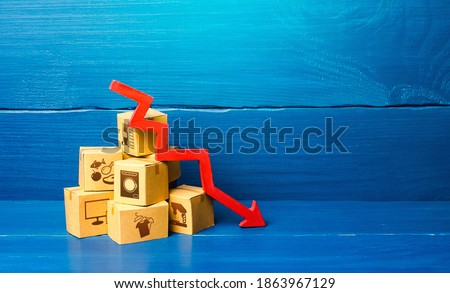 Cardboard boxes and red down arrow. Decline in sales and production volumes. Depressed economy. Low business activity. Economic recession, skepticism and pessimism. Competitiveness of national goods. Сток-фото ©