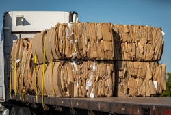 Cardboard boxes broken down and pressed into bales and loaded onto a flatbed truck