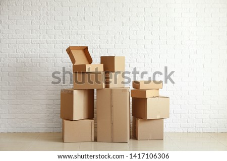 Cardboard boxes near white brick wall