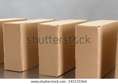 Cardboard boxes on conveyor belt, on grey background