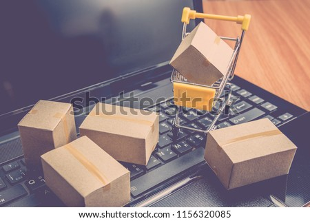 Cardboard boxes or cartons and trolley on laptop. Online shopping e-commerce and logistic shipping freight delivery transportation.  Customer can purchase product items on internet website at home.