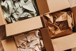 Cardboard boxes with crumpled paper inside for packaging goods from online stores, eco friendly packaging made of recyclable raw materials