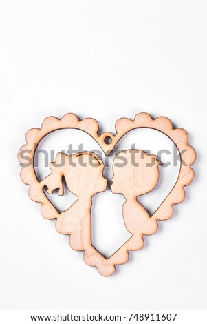 Cardboard card with kissing boy and girl. Wooden heart with lovers inside, isolated on white backgroud. Cute gift on BValentine Day. #748911607