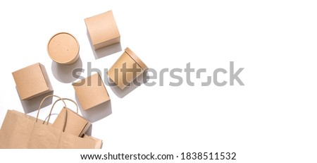 Cardboard containers for food, drinks and items drop out of the craft bag.  Isolated on white background, top view. Copy space. Delivery, takeaway food, eco-friendly packaging concept. Nobody. Photo stock ©