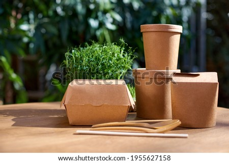 Cardboard containers for food, drinks, items. Copy space. Delivery, takeaway, zero waste, eco production packaging concept, variety of paper takeout containers to client at house and hanging outside. Photo stock ©