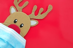 Cardboard cutout of a red-nosed reindeer peeking while wearing a face mask. Covid during Christmas season concept. Red background with copy space.