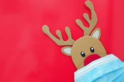 Cardboard cutout of cute reindeer peeking while wearing a face mask. Covid during Christmas season concept. Red background with copy space.