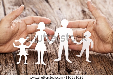 Cardboard figures of the family on a wooden table. The symbol of unity and happiness. Hands gently hug the family.