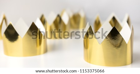 Cardboard golden crowns lying on a white table. Minimalistic style. #1153375066