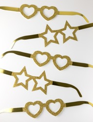 Cardboard golden eyeglasses in the shape of stars and hearts lying on a white table. Minimalistic style. Top view. Flat lay.