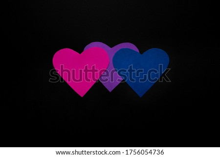 Cardboard hearts in the colors of the flag of bisexuals on a black background: purple, blue and lavender Stockfoto ©