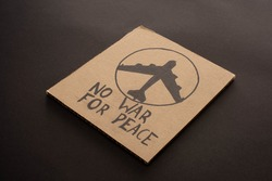 cardboard placard with no war for peace lettering and airplane on black background