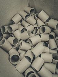 Cardboard spools for winding. Reels made of cardboard. Background of cardboard bobbins. Defocused, blur, selective focus, grain, noise