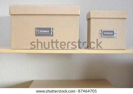 Cardboard storage boxes on shelf against plain wall.