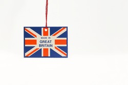 Cardboard tag on a string with a flag and the inscription made in great Britain. Close- up, white isolated background.