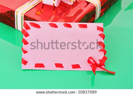cardboard tags with red ribbon bow and gift box   on green background