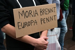 Cardboard with German text Moria brennt, Europa pennt (Moria is burning, Europe is sleeping) on a demonstration in Lubeck for accommodation of refugees after the fire in the Greek refugees camp