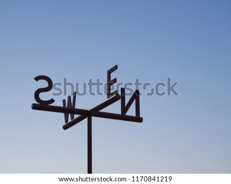 Cardinal Direction Direction pointer Sign against blue sky. Directions North, South, East, West are denoted by their initials N, E, S, and W on the metal plates.