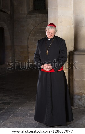 Cardinal standing against a pillar in his medieval 14th century church