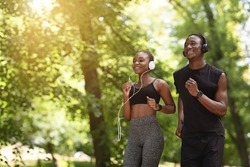 Cardio Training. Positive African American Couple Jogging Together In City Park, Copy Space