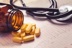Cardiogram, stethoscope and yellow pills. Low contrast, toned photo.