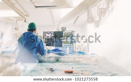 Cardiologist doing catheter ablation with radiofrequency energy using imaging system with fluoroscopic X-ray tube for interventional vascular procedures and electrophysiology. image guided system