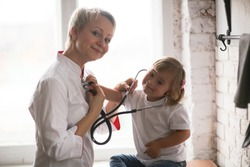 Cardiologist listens to the heart of a child with Down syndrome, the concept of health and medical examination of children with special needs