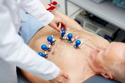 Cardiologist putting special equipment on chest of patient before making ecg