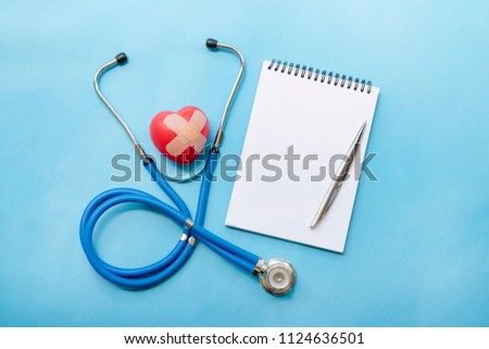 Cardiologist's day; the day of the doctor; heart diseases; Cardiology stethoscope blue with red hearts, a notebook and pen on a blue background; diagnosis of diseases of the heart