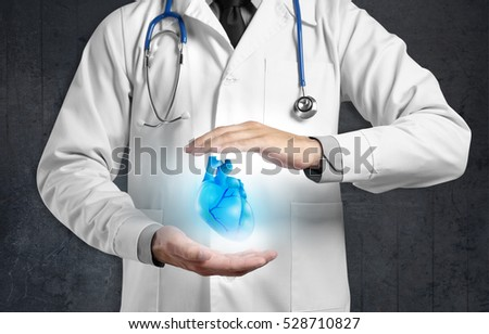 Cardiologist with heart in hands, closeup. Dark background. Cardiology concept.