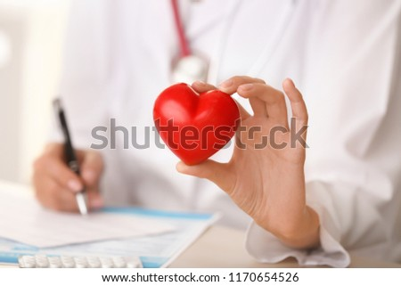 Cardiologist with red heart in clinic, closeup #1170654526