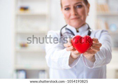 Cardiologist with red heart in medical concept #1054193825